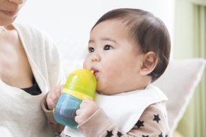 ベビーマグでお茶を飲む赤ちゃん